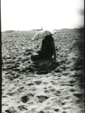A Young Woman Sitting on a Sandy Beach Holding a Sun Shade Photographic Print by Leonora Saunders