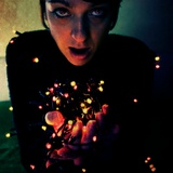 A Young Woman Holding a Handful of Christmas Lights Photographic Print by Kimberley Ross