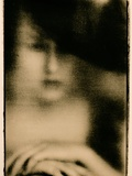 Dark Lith Portrait of Young Woman in Large Dark Hat, Hands Resting on Chair Photographic Print by Susan de Witt