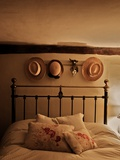 Floral Cushions on Striped Duvet on Old Iron Double Bed with Straw Hats Hanging with Silver Heart Photographic Print by Tim Kahane