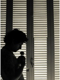 A Young Man Standing Infornt of a Window Holding a Small Flower Photographic Print by Marco Diaz