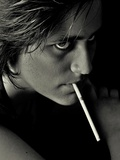 The Face of a Young Man Smoking a Long Cigarette Photographic Print by Martina Zancan