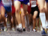 Blurred Action of Runner's Legs Competing in a Race Photographic Print