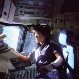 Astronaut Sally Ride Monitors Control Panels from Pilot's Chair of Space Shuttle Challenger Photo