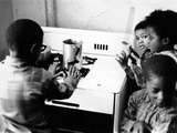 Four African American Children Cluster around the Gas Stove for Warmth Photographie