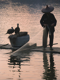 Fisherman Fishing with Cormorants on Bamboo Raft on Li River at Dusk, Yangshuo, Guangxi, China Photographie par Keren Su