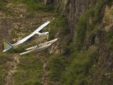 A Bush Pilot Flies His Float Plane Close to Mountain in Alaskan Canyon, USA Photographic Print by John Alves