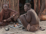 Elderly Himba Married Couple Sitting Near a Small Fire Outside their Hut, Purros Village, Namibia Photographic Print by Kim Walker