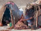 Himba Woman Sitting on Ground Fanning a Small Fire Outside Two Huts, Himba Village, Purros, Namibia Photographic Print by Kim Walker
