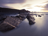 Long Exposure of Waves Moving over Rocks on Crackington Haven Beach at Sunset, Cornwall, England Photographic Print by Ian Egner