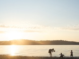 Silhouette of Mother Taking Pictures of Children at Sunset, Vashon Island, Washington State, USA Photographic Print by Aaron McCoy