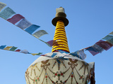 Prayer Flags Flying in Wind Above Prayer Wheel, Shangri-La (Zhongdian), Yunnan Province, China Photographic Print by Lynn Gail