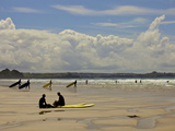 Surfers with Boards on Perranporth Beach, Cornwall, England Stampa fotografica di Simon Montgomery