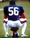 Lawrence Taylor Sitting on Football and Helmet Vertical Photo