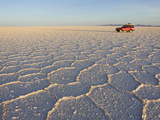 A Red Truck in the World's Largest Salt Flats in Salar De Uyuni Photographic Print by Mike Theiss