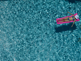 A Girl Floating on a Pink Raft in a Swimming Pool Photographic Print by Jodi Cobb