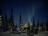 Aurora Borealis over a Home in a Snowy Landscape with Evergreen Trees Photographic Print by Norbert Rosing