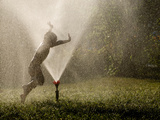 A Boy Plays in a Sprinkler on a Hot Summer Day Photographie par Heather Perry
