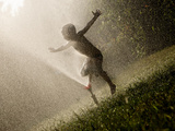 A Boy Plays in a Sprinkler on a Hot Summer Day Photographic Print by Heather Perry