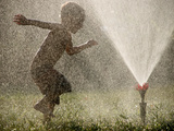 A Boy Plays in a Sprinkler on a Hot Summer Day Reproduction photographique par Heather Perry