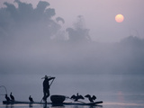 A Fisher Uses Cormorants to Capture Fish from the Li River at Sunrise Photographie par Kenneth Ginn