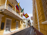 A View Down a Street Lined with Yellow Buildings and Flying Flags Photographic Print by Mike Theiss