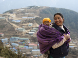 A Woman Carries Her Baby in a Blanket with Namche Visible Behind Photographic Print by Alex Treadway