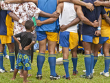 A Rugby Team in Huddle with a Child Watching Between Adults Photographie par Richard Nowitz
