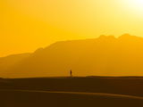 A Lone Man Walks on Top of Sand Dunes During Sunset Photographic Print by Mike Theiss