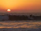 Surfer Riding a Wave at Sunset over the Pacific Ocean Reproduction photographique par Tim Laman