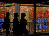 Women Walk Past Neon Signs in the Mong Kok District Photographic Print by Tino Soriano