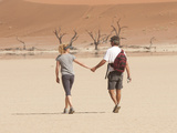 A Couple Holds Hand While Walking Through a Sand Dune Park in Namibia Photographie par Pete McBride