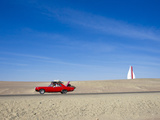 A Red Car Packed Full Lof Luggage Traveling on a Desolate Road Photographic Print by Mike Theiss