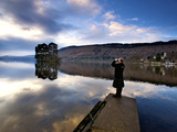 A Man Uses Binoculars to Look Out over a Still Lake Photographic Print by Jim Richardson