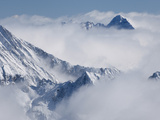 Aerial View of Snowcapped Peaks Poking Through the Clouds in Colorado Photographic Print by Pete McBride