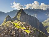 Sun Shining Through the Andes Mountains onto Machu Picchu at Sunset Impressão fotográfica por Mike Theiss