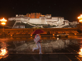 A Pedestrian in Front of the Potala Palace on a Rainy Night Photographic Print by Michael S. Yamashita