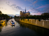 The Seine at Sunset with Notre Dame in the Background and a Tour Boat Photographie par Jorge Fajl