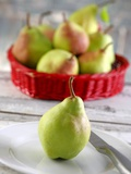 A Pear on a Plate in Front of a Basket of Pears Photographic Print by Jean-Paul Chassenet