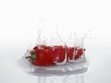 A Red Chilli Pepper Falling into Water Photographic Print by  Kröger & Gross