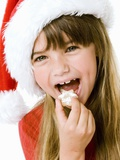Girl in Father Christmas Hat Eating Biscuit Photographic Print