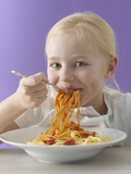 Blond Girl Eating Spaghetti with Tomato Sauce Photographic Print by Kai Schwabe