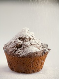 Sprinkling a Chocolate Muffin with Icing Sugar Photographic Print