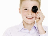 Boy Covering One Eye with a Liquorice Wheel Photographic Print