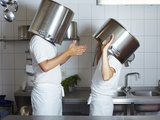 Two Chefs Having Discussion with Large Pans on their Heads Photographic Print by Robert Kneschke