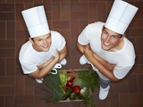 Two Chefs with their Arms Folded Beside Crate of Vegetables Photographic Print by Robert Kneschke