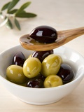 Green and Black Olives in Small Dish and on Wooden Spoon Photographic Print by Barbara Kraske