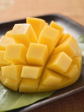 Diced Mango Still Attached to the Skin on Brown Plate Reprodukcja zdjęcia