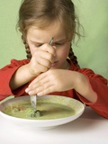Girl Cutting a Broccoli Floret in Vegetable Soup Photographic Print by Ulrike Koeb