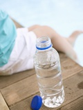 Child Sitting Beside Bottle of Water on Edge of Pool Photographic Print